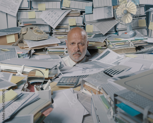 Fotografia Disappointed stressed businessman overwhelmed by paperwork