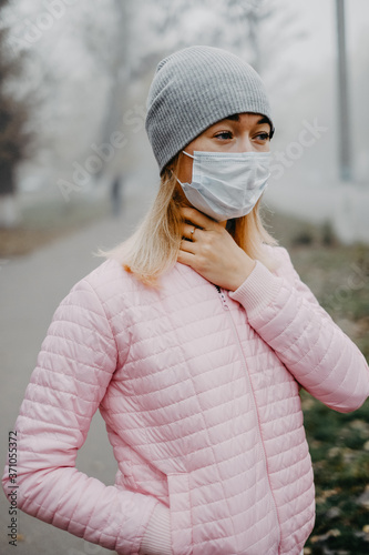 Fototapety, obrazy: A young woman is standing near the road in a medical mask.