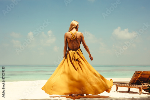 Rear view of young woman in yellow dress standing on beach - 371059355