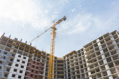 Canvas Print Crane and building construction site against blue sky