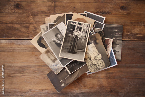 old vintage monochrome photographs in sepia color are scattered on a wooden tabl Wallpaper Mural
