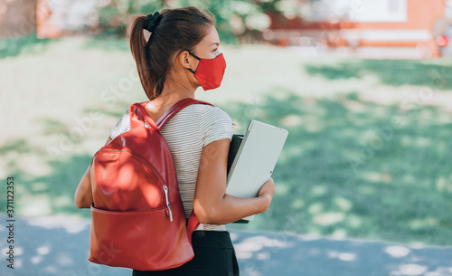 Fotografija Back to school university student girl wearing covid mask walking on campus with backpack, books and laptop