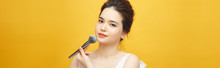 Beautiful Woman Holding Makeup Brush Over Yellow