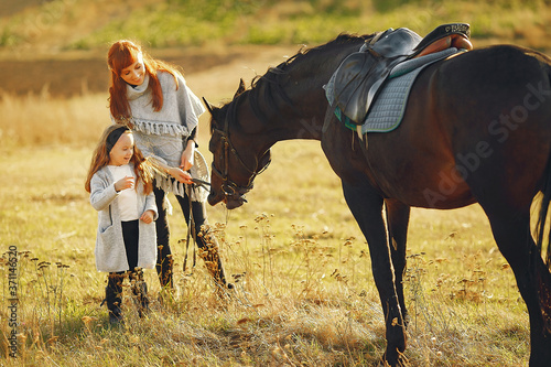 Fotografie, Obraz Mother and daughter next to horse