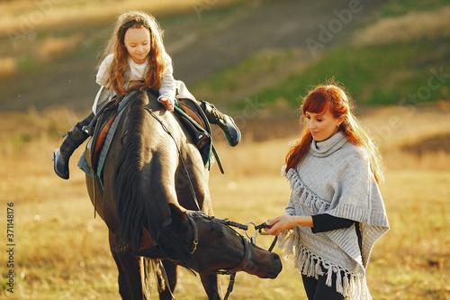 Obraz na plátně Mother and daughter next to horse