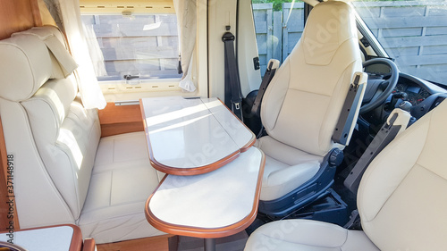 Fotografija vacation campervan with luxury white interior table wooden and seat in modern mo
