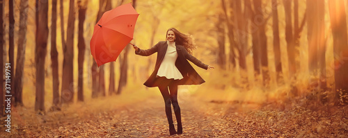 Fototapeta young woman dancing in an autumn park with an umbrella, spinning and holding an umbrella, autumn walk in a yellow October park obraz