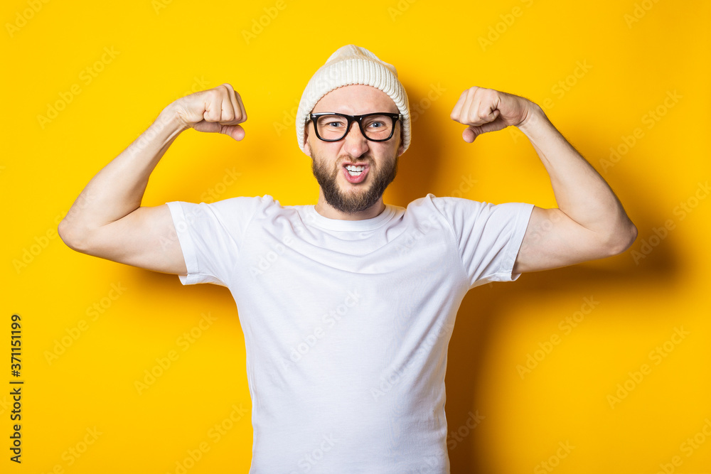 Fototapeta Bearded young man shows muscles with his hands, masculine strength on a yellow background