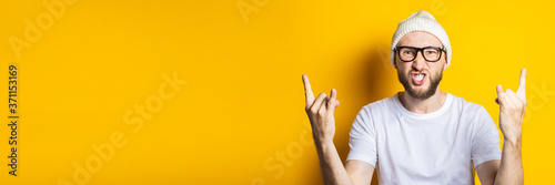 Obraz na plátně Bearded young man with glasses shows a rocker goat gesture on a yellow background