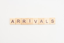 Word ARRIVALS Made From Wooden Cubes On White. Travel Concept.