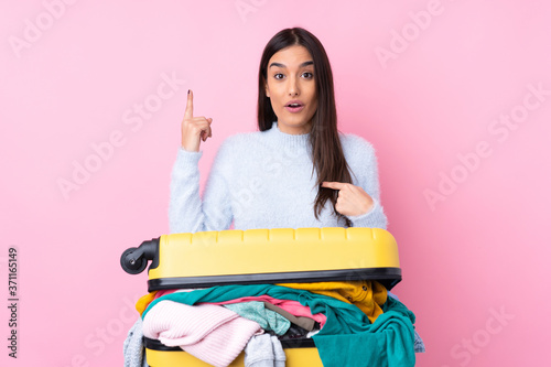 Traveler woman with a suitcase full of clothes over isolated pink background wit Canvas Print