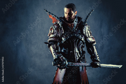 Fotomural Powerful knight in the armor with the sword. Dark background.