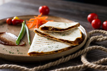 Quesadilla On A Plate On The Table In A Cafe. Three Pieces Of Pita Bread With Filling On A Brown Plate With Vegetables And Sauce