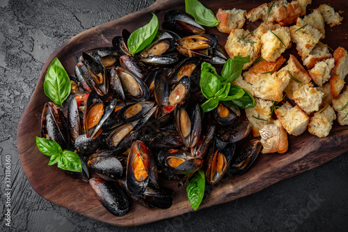 Fotografie, Obraz Delicious cooked mussels in sauce with dried baguette
