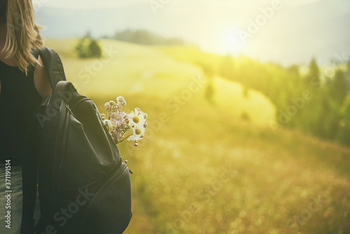 Photo Girl tourist with a backpack and a bouquet of flowers on the background of a mountainous green landscape