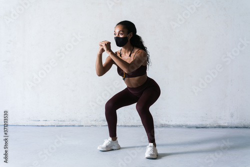Photo Photo of athletic african american woman in face mask doing exercise