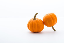 A Pair Of Mini Pumpkins Next To Each Other On White Surface With White Background, With Subtle Gradients.  Small Pumpkins For Decoration Up Close.