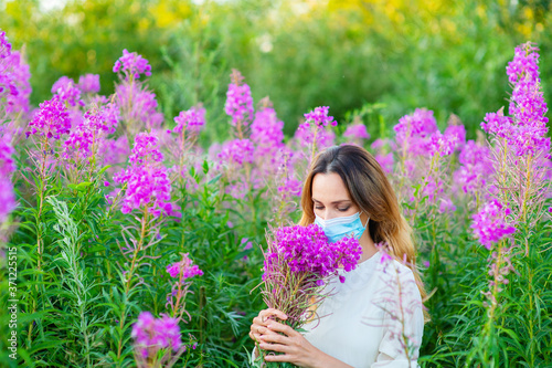 Photo A girl in a medical mask sniffs a bouquet of purple flowers in her hands