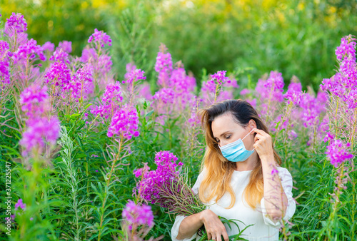 A girl in a medical mask holds a bouquet of purple flowers in her hands Canvas Print