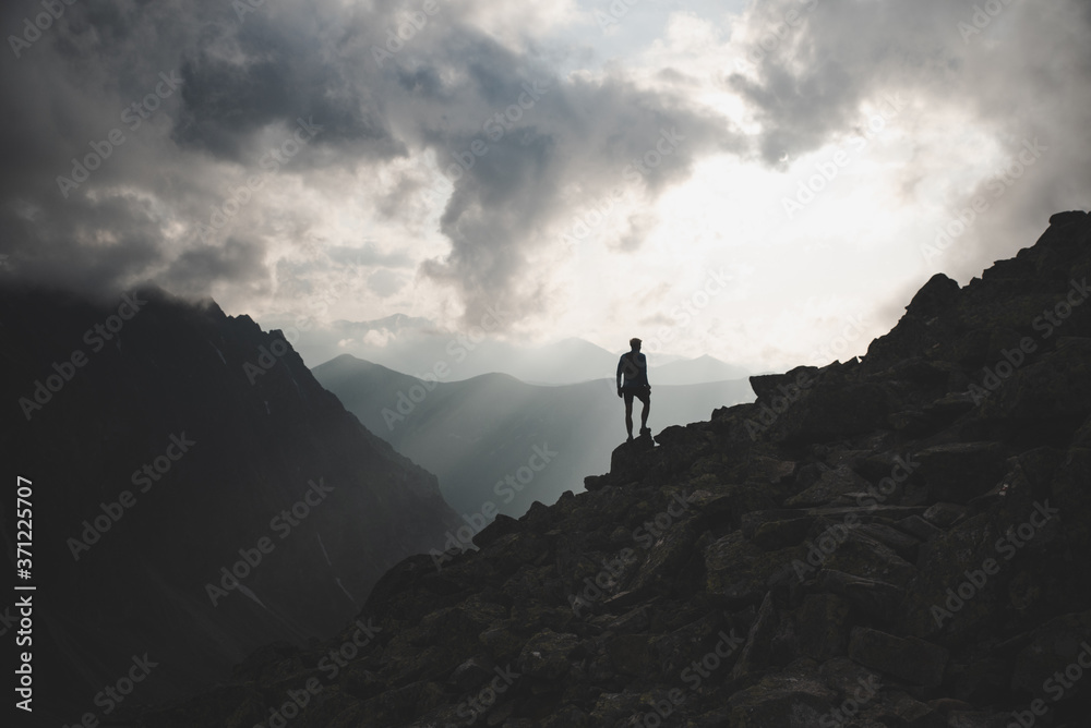 Fototapeta Man in mountains, silhouette of young hiker, sunset sky and hills in background--