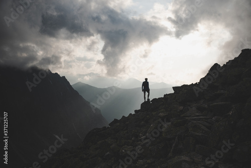 Fototapeta Man in mountains, silhouette of young hiker, sunset sky and hills in background-