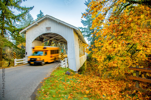 Valokuvatapetti School bus emerging from Hannah covered bridge near Sio, Oregon, blurred to show