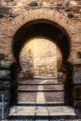 Fotografie, Obraz Ancient Moorish stone arch that leads to a narrow alley, illuminated by an old lantern