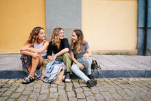 Women Browsing Smartphone Sitting On Asphalt Ledge In Street