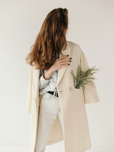 Anonymous Woman With Plant In Coat