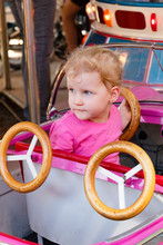 Toddler Sitting In Fairground Ride