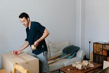Young Man Closing A Cardboard Box.