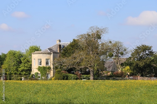 A Georgian house situated next to a  wild flower meadow in Gloucestershire, England Canvas Print