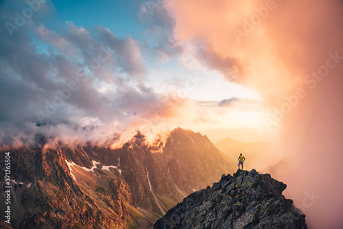 Fototapeta Man in mountains, silhouette of young hiker, sunset sky and hills in background