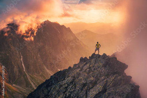 Man in mountains, silhouette of young hiker, sunset sky and hills in background Travel, adventure or expedition concept Fototapete