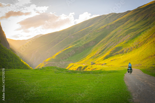 Fotografering Cyclist on gravel road surounded by the mountains going to he valley