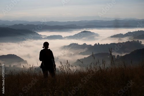 Plakaty do sypialni  young-woman-standing-on-golden-meadow-and-watching-towards-the-sunrise-above-mist