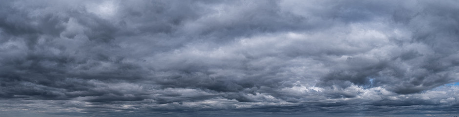 Panorama of Cumulus fluffy white and dark grey storm clouds against sky background.