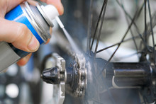 Hand Holding Spray Lubricant In His Hand To Lubricate The Bike Chain