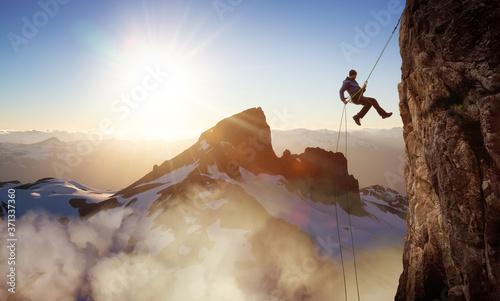 Fényképezés Epic Adventurous Extreme Sport Composite of Rock Climbing Man Rappelling from a Cliff