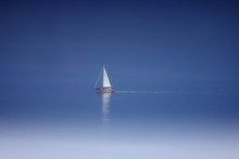 Beautiful Lonely White  Sailboat In The Middle Of The Sea