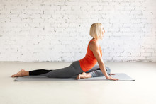Attractive Caucasian Woman Does Pigeon Pose Sitting On A Mat, In Loft White Studio. Indoor Workout, Selective Focus.