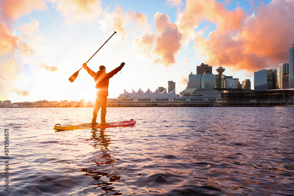 Fototapeta Adventurous man is paddle boarding near Downtown City during a vibrant winter sunrise. Taken in Coal Harbour, Vancouver, British Columbia, Canada. Colorful Sky Overlay