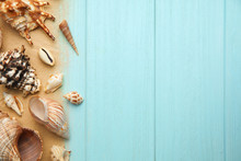 Different Sea Shells And Sand On Light Blue Wooden Table, Flat Lay. Space For Text