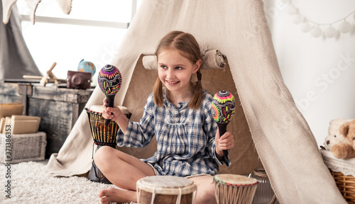 Tablou Canvas Happy little girl playing on wooden maracas in kids room decorated with ethnic d