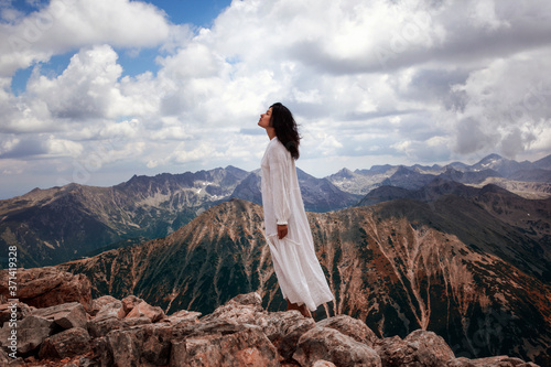 God Is A Woman. A woman in a white dress on the highest mountain in Bulgaria