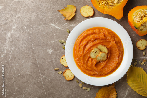 Composition with plate of pumpkin puree with croutons on gray background, top view