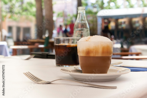Fototapeta Cappuccino on table in Mediterranean cafe with blurred background