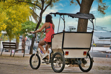 Young Girl Driving The Electric Pedicab On The Seafront. Pedicab, The Most Innovative And Ecological Transport To Know Any Country.