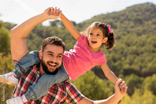 Father playing with daughter near to olive tree Canvas Print