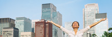 Happy Asian Woman With Open Arms Up To The Sky Breathing Fresh Air In City Downtown Buildings Background. Businesswoman At Office Work Smiling Banner Panorama.